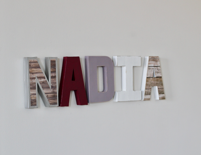 Baby girl name sign spelling out Nadia in different colors and textures.