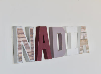 Baby girl nursery sign in purples and whites spelling out Nadia.
