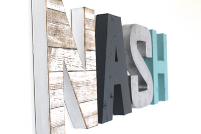 Modern farmhouse nursery letters spelling out the name Nash in white, gray, blue, and silver colors.