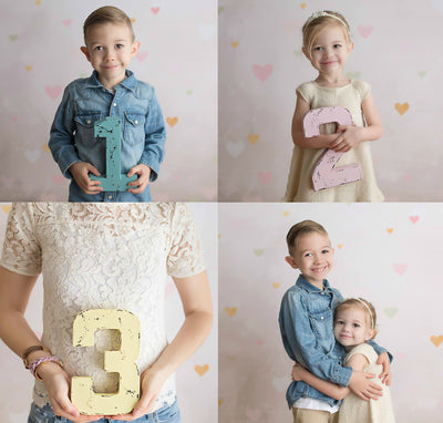 """Wooden"" numbers for Pregnancy announcement with a little boy and little girl holding up numbers in different colors."