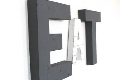Modern farmhouse EAT sign in dark gray letters and a plank shiplap style letter.