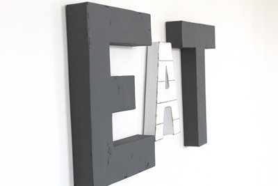 EAT wall sign letters in gray and white shiplap colors.