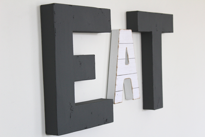 Modern rustic farmhouse EAT Sign in gray and white letters.