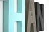 Nursery letters in aqua blue, grey, and black colors.