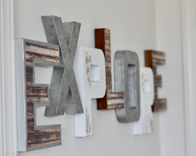 Explore sign for aviation nursery decor in browns, silvers, and white.