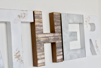 Distressed wall letters in white, brown, and silver.