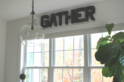 "Black distressed ""wooden"" gather wall sign in a modern farmhouse kitchen nook."