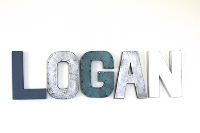 "Wall nursery letters spelling out the name Logan in blue and silver ""metal"" letters."
