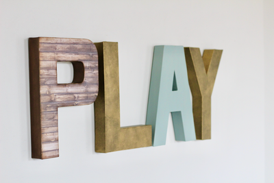Play sign in browns, gold, and blue for kids playroom decor.