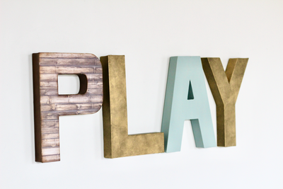 Playroom decor wall sign in gold, brown, and soft blues.