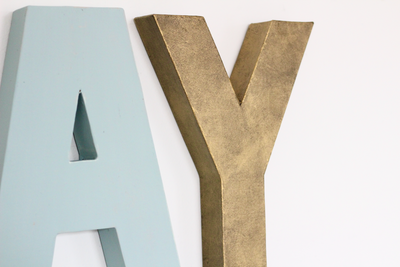 Blue wall letter A and industrial gold letter Y for kids playroom decor.