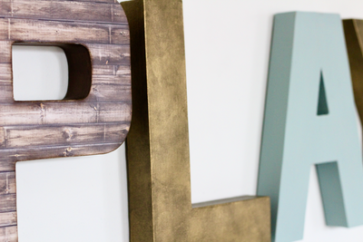 Farmhouse brown letter P and gold letter L for kids playroom decor.