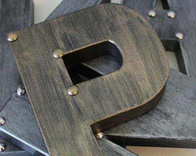 "Metal ""P"" in a bronze finish with bronze studs on corners"