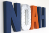 Camping themed nursery letters spelling out the name Noah in blues, oranges, and whites.