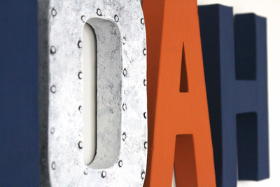 Custom wall letters in industrial white colors and modern oranges and navy colors.