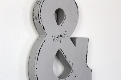 Grey wall letter ampersand sign.