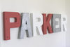 Girls name sign letters spelling out Parker in pink, silver, and white colors.