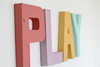 Girls pastel play letters in different soft pastel colors spelling out the word PLAY.
