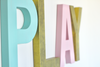 Gender neutral playroom sign in three different colors: gold, aqua, and pink.