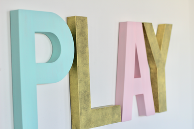 Gender neutral play sign in aqua, gold, and pink.