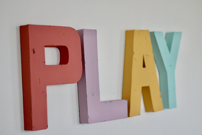 Pastel play sign in pinks, yellows, and blues.