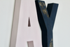 Distressed navy letter Y and a soft pastel pink letter A.