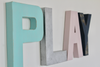 Pastel playroom wall decor play sign letters in soft pink and blue colors.
