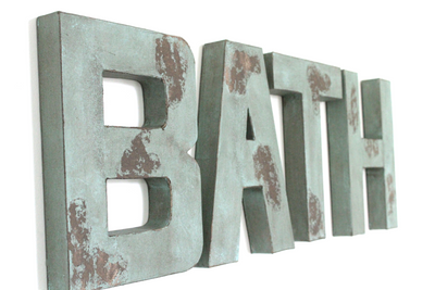 Bathroom wall letters in a blue/green distressed color.