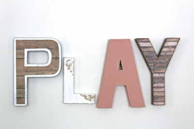 "Play wall sign in reclaimed ""wooden"" letter in brown, white, and pink."
