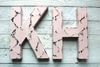 Pink girl letters K and H in a distressed style