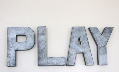 "Play wall sign done in a gray zinc ""metal""."