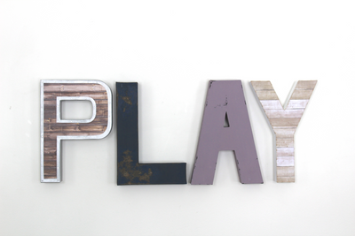 Play sign for girl's playroom wall decor in purple, navy, white, and brown letters.