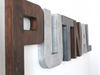"Boy room wall letters spelling out the name ""Putnal"" in ""wooden"" brown letters and gray ""metal"" letters."