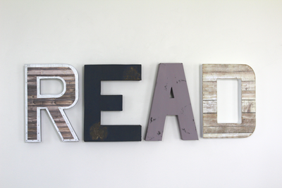 Read wall letters for playroom wall decor in brown, navy, purple, and white letters.