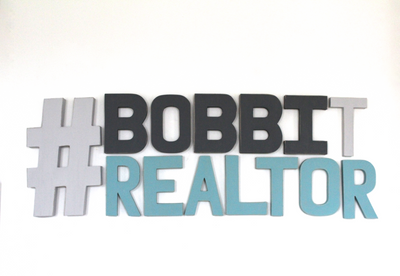 Realtor office wall sign in gray and blue with hashtag.