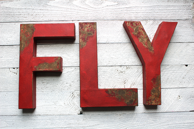 "Large ""wooden"" FLY letters in a distressed red color"