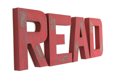 Red distressed faux wooden letters spelling out the word READ for playroom and nursery wall decor.