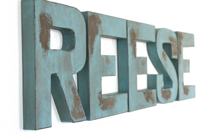 Distressed wall letters spelling out Reese for rustic farmhouse nursery decor.