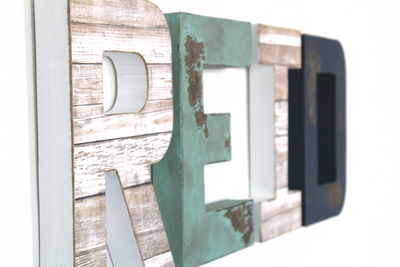 Beach themed nursery letters spelling out Reid in different coastal colors and textures.