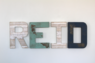 Reid nursery letters in beach beige colors mixed in with worn and weathered patina colors and navy distressed letters.