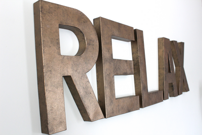 "Large custom word in relax in ""metal"" bronze"