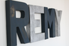 Travel theme nursery wall letters spelling out the name Remy for boys room decor.