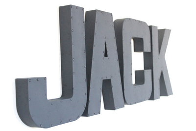 Wall name letters spelling out Jack in an industrial farmhouse style with a nail trim design.