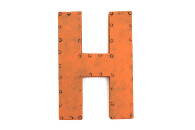 Orange wall letter H with a nail trim design.