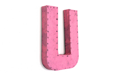 Bright pink retro barn letter U with a metal nail head trim.