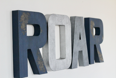 Roar sign in navy, silver, and grey.