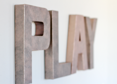 Pink wall letters spelling out the word PLAY for girls playroom art wall.
