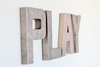 Pink play wall sign in rose gold faux metal.
