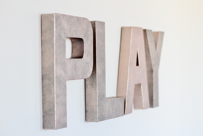Rose gold pink faux metal wall letters spelling out the word PLAY for girls nursery wall art and playroom.