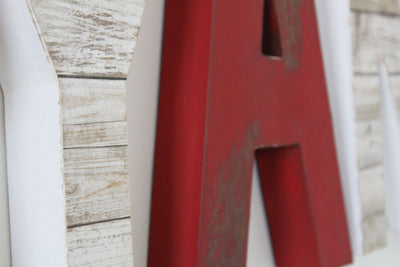 Distressed red letters and white faux reclaimed wooden letters.